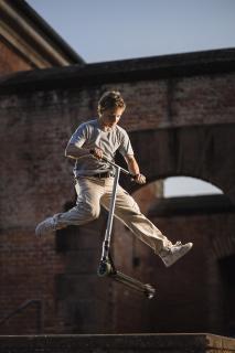 Portrait - ein Junge macht Scooter-Tricks