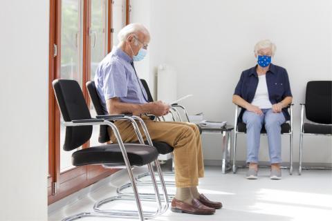 Eine alte Frau und ein alter Mann in einer Arztpraxis
