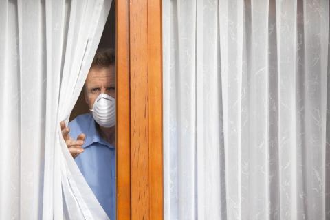 Mann mit Alltagsmaske schaut aus dem Fenster