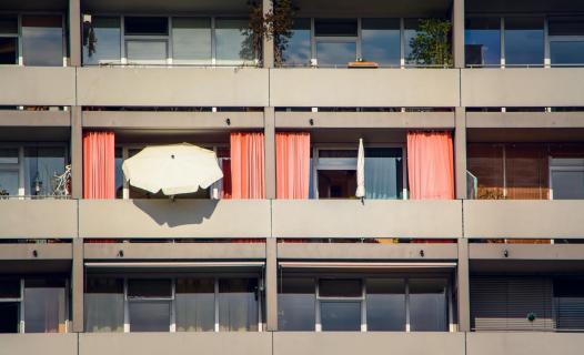 Wohnblock mit Schirm und Gardine