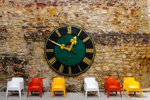 Uhr mit bunten Stühlen