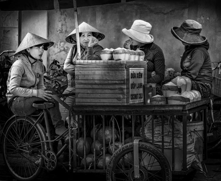 IDEE: Die Kokosnuss-Verkäuferinnen in Hôi An in Vietnam. Die vier Frauen unterhalten sich während ihrer Mittagspause miteinander und bilden mit Wagen, Früchten und ihren Hüten eine Einheit. GESTALTUNG: Sehr gefallen die Wiederholungen der...