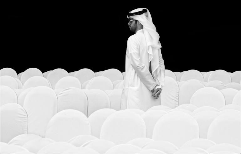 IDEE: Ein in sein traditionelles Gewand gekleideter Veranstaltungsbesucher in einer Halle in Dubai. Er bildet mit seiner Kandora ein sehr leicht wirkendes Ensemble mit den mit Hussen überzogenen Stuhlreihen. GESTALTUNG: Gut herausgearbeitete Formen. Überzeugt vor allem durch die Weißtöne vor dem satten Schwarz des Hintergrunds. TECHNIl: Zufällig bei den Hipa-Awards vor der Preisverleihung gesehen und aus der Hand heraus mit Hallenbeleuchtung fotografiert. Leichte Belichtungskorrektur nach oben.