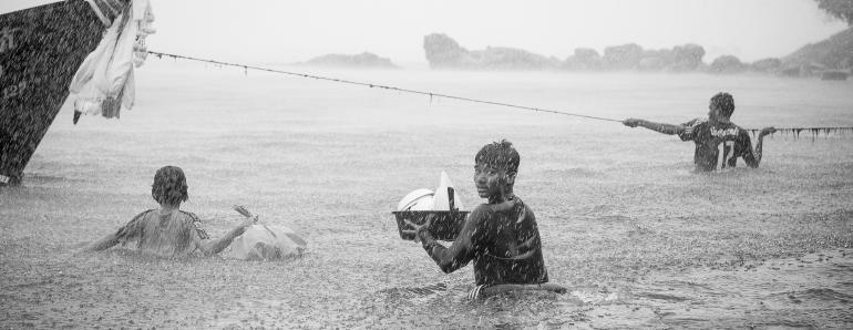 IDEE: Während eines Unwetters in Thailand bringen sich die Fischer auf ihren Booten ins Trockene – und müssen zunächst mit ihren Habseligkeiten durch das Wasser waten. GESTALTUNG: Der Anschnitt deutet die Situation an – mehr muss man von Landschaft und Boot nicht sehen. Toll der perfekte abgelichtete Regen und natürlich der Blick zurück. TECHNIK: Der bereits durchnässte Fotograf wagte sich aus seiner kümmerlichen Deckung und folgte den Fischern, um das einzige Foto – natürlich freihand – zu machen.