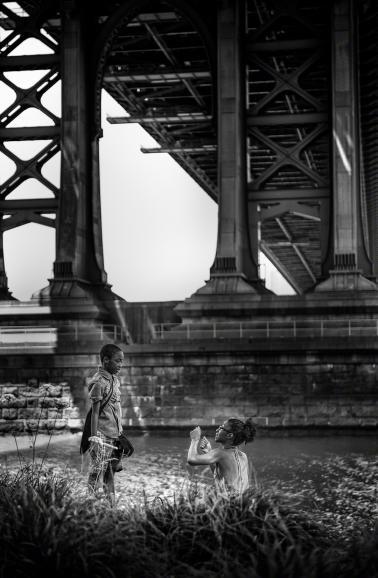 IDEE: Die monumentalen Pfeiler der Manhattan-Bridge bilden einen Widerspruch zu der leicht wirkenden Picknick-Szene unten. GESTALTUNG: Die Schärfe liegt exakt auf den beiden diskutierenden Personen. Sehr gut gefällt das schräg einfallende Licht, das Mutter und Sohn vom Hintergrund löst. TECHNIK: Zufallsfund auf der Brooklyn-Seite. Der Fotograf schlenderte durch den Park unter der Brücke. Spontan und freihand.