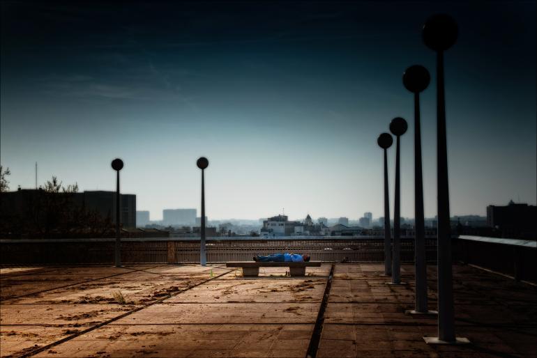 IDEE: Hoch über den Dächern von Brüssel macht ein Arbeiter in einer leicht surreal anmutenden Umgebung seine Pause. GESTALTUNG: Das Blau der Kleidung bildet einen schönen Kontrast zu den sanften Ockertönen der seltsamen Umgebung. TECHNIK: Freihand fotografiert. In der Bildbearbeitung wurde die Vignette verstärkt. Außerdem legte der Fotograf einen radialen Unschärfeverlauf an, so dass die Lampen als Rahmen fungieren und den Blick auf den schlafenden Mann fokussieren.