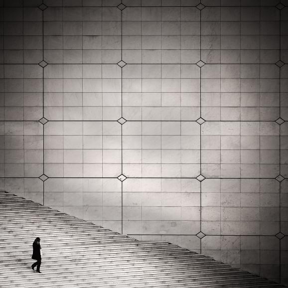 IDEE: Streetphotography als Architekturfoto: Die kleine Person scheint in der mächtigen Konstruktion des Grande Arche in Paris zu verschwinden und macht diese noch größer. GESTALTUNG: Exakt gesetzte Linien dominieren das Bild und stellen die Architektur in den Mittelpunkt. Sehr gut gefällt, dass das Umfeld aus dem Foto ausgeklammert wurde. TECHNIK: Zufallsfund im eigentlich sehr belebten Viertel La Défense, der Fotograf hatte nur ein paar Sekunden. Beschnitt und Vignette in der Bildbearbeitung durchgeführt.
