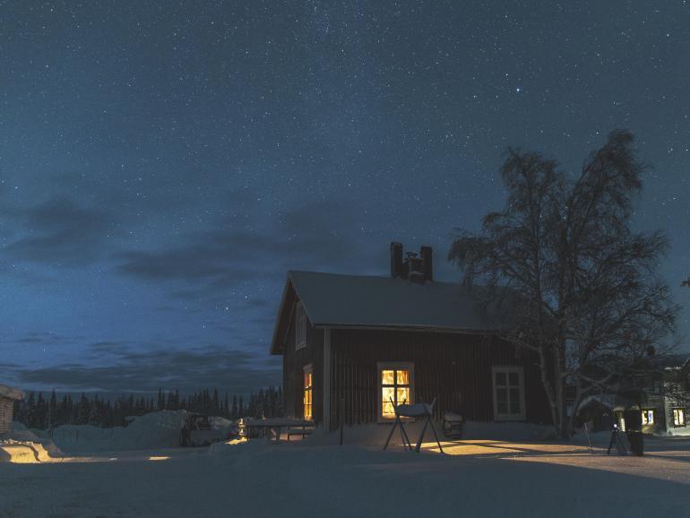 Winterromantik pur: Die Petroleumlampe in der Küche der Blockhütte im Wildnisdorf Solberget bringt Licht in die sternenklare Nacht.