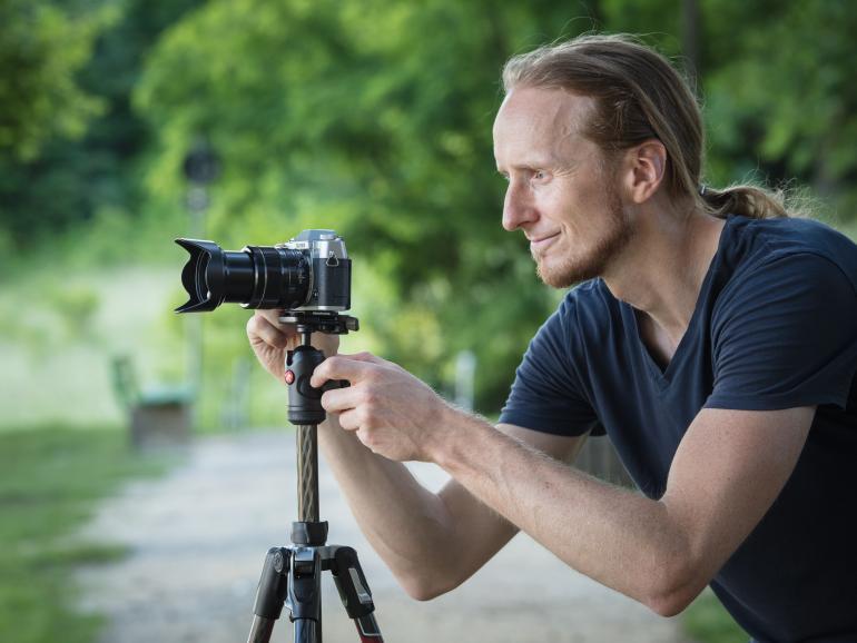 Fotograf Michael Breitung bei der Arbeit. Hier hat er seine Systemkamera auf der Carbon-Versionen des Befree Advanced Stativs von Manfrotto befestigt. Mit dem kompakten Reisestativ fuhr er unter anderem nach Regensburg und fotografierte das Stadtpanorama an einem warmen Sommerabend.